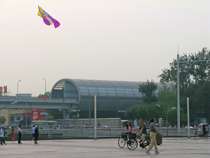 Everyday life on a pedestrian square, a kite in the sky