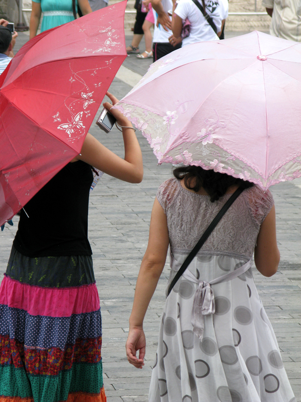 Sun umbrellas protect young Chinese tourists